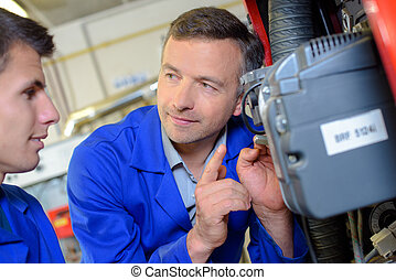 Teacher looking at motor, giving warning to apprentice