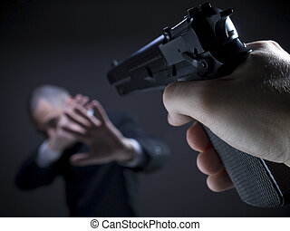 Point and shoot - A threatening hand pointing a gun on an...