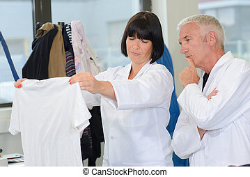 Man and woman in laundrette looking at T-shirt