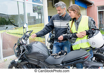 Man explaining controls of a motorcycle to a lady