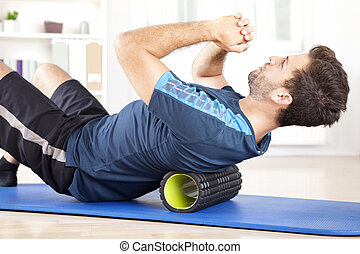 Man Lying on a Foam Roller While Doing an Exercise -...