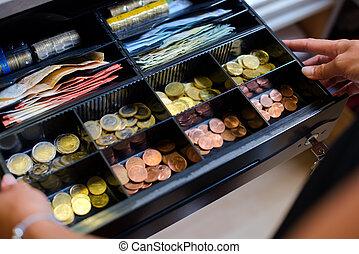 Open cash till containing Euros
