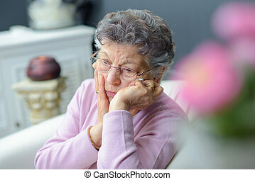 Forlorn elderly lady sitting alone