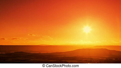 sunset scene with sun fall behind the mountains and clouds in background, time lapse shot, warm colorful sky with soft clouds 4K and HD