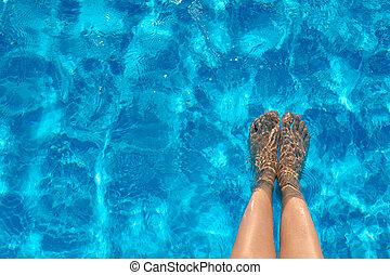 Female legs in the pool water in summer.