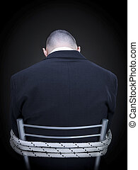 Tied up - A businessman is tied up on a chair turning his...