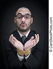 Puzzled businessman - A man on a suit shows his tied hands...