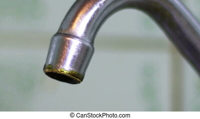 Water Dripping from a Tap - Water drips from the tap in the...