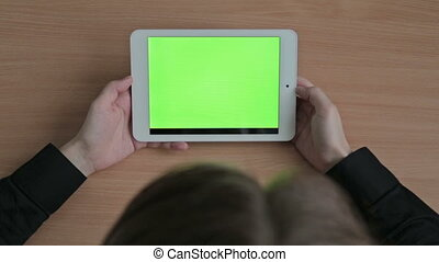 Woman watching videos on tablet, green screen, HD