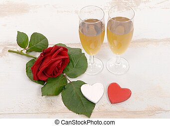 two glasses of champagne and red roses