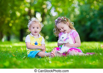Kids playing with real rabbit - Children play with real...