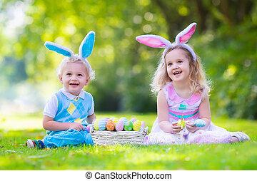 Kids on Easter egg hunt - Little boy and girl having fun on...