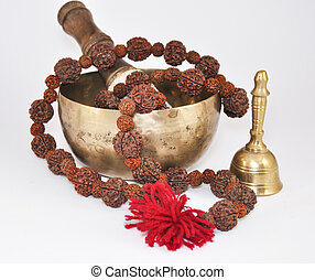 Tibetan Singing Bowl with beads and metal bell on a white...