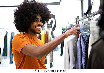 Customer looking for clothes to buy in store - Smiling...