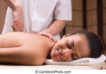 Woman and spine mobilization - Young happy woman in spa...