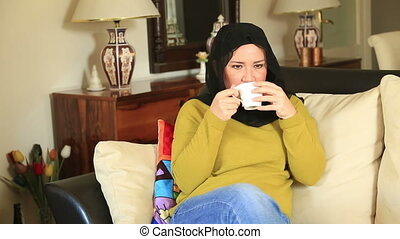 Muslim woman drinking coffee - Portrait of a muslim woman...