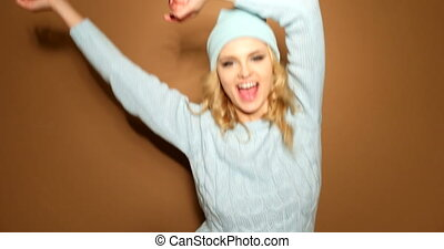smiling blonde woman in winter jumper and hat jumping on...
