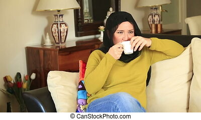 Muslim woman drinking coffee - Muslim woman sitting on a...