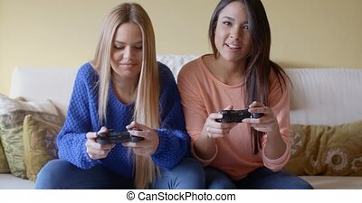 Excited girls playing video games at home - Front view of a...