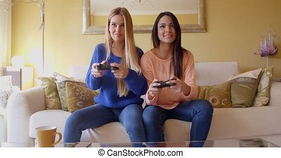 Laughing young female video game players - Front view of...