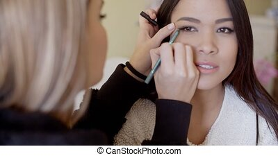 Serious woman getting eye liner makeup - Rear view of blond...