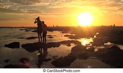 couple walking on the beach at suns