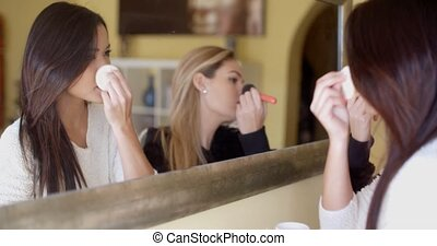 Girls Putting Make-up In Front of a Mirror - Two Young Women...