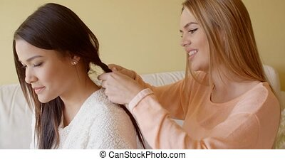 Pretty Woman Fixing the Hair of her Friend - Kind Pretty...