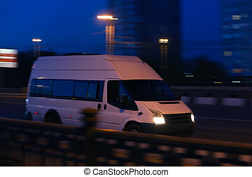 minibus moves down the street at night - white minibus moves...