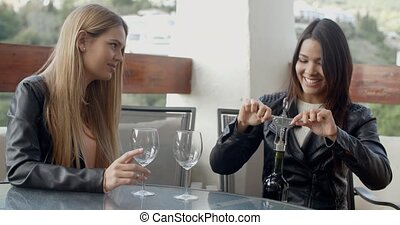 Two friends opening wine bottle - Two young adult female...