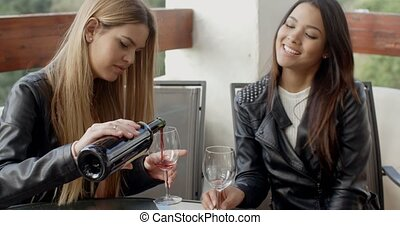 Friend pouring woman wine at table - Cute female friends...