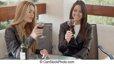 Two attractive girls sitting on balcony with wine - Two...