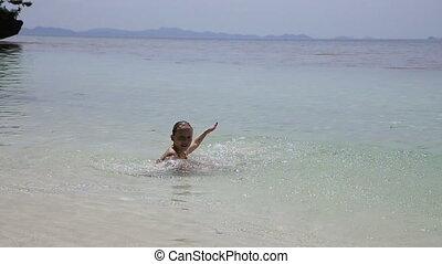 Little girl playing on beach - Young girl playing in the...