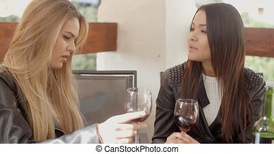 Woman talking to friend over wine - Woman holding wine glass...