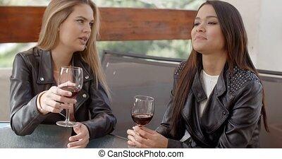 Two beautiful girlfriends sitting on terrace