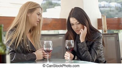 Blond woman comforting friend over glass of wine - Blond...