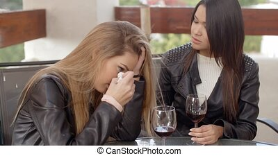 Pair of sad women drinking wine - Devastated friend with...