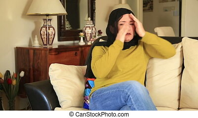 Muslim woman having headache - Muslim woman sitting on a...