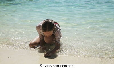 Happy child playing with sand on beach in summer.