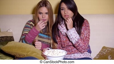 Two Girls Watching a Movie Seriously with Popcorn