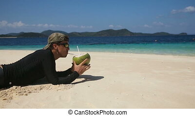 Man on the beach drinking coconut juice - Man drinking...