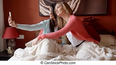 Girls Taking Selfie Using Phone in their Bedroom - Two...