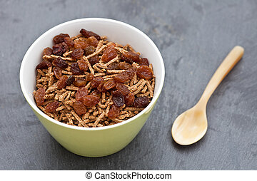Bran breakfast cereal with sultanas in a green bowl