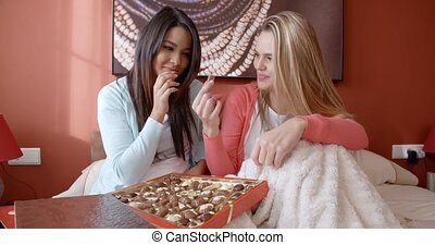 Two adorable women snacking on chocolates - Pair of smiling...