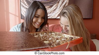 Two adorable women snacking on chocolates