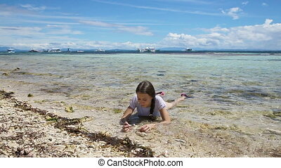 Happy child playing with sand on beach in summer. - Young...