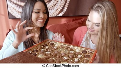Two playful ladies choosing chocolate snacks - Two playful...