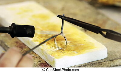 Process of soldering gold ring by torch. Production and...
