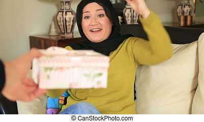 Muslim woman opening the gift box - Portrait of beautiful...