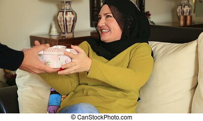 Muslim woman opening the gift box - Portrait of muslim woman...